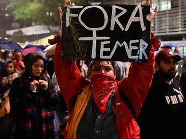 """A demonstrator carries a sign that reads in Portuguese """"Get out Temer"""" to protest Brazilian President Michel Temer in Sao Paulo, Brazil. AP"""
