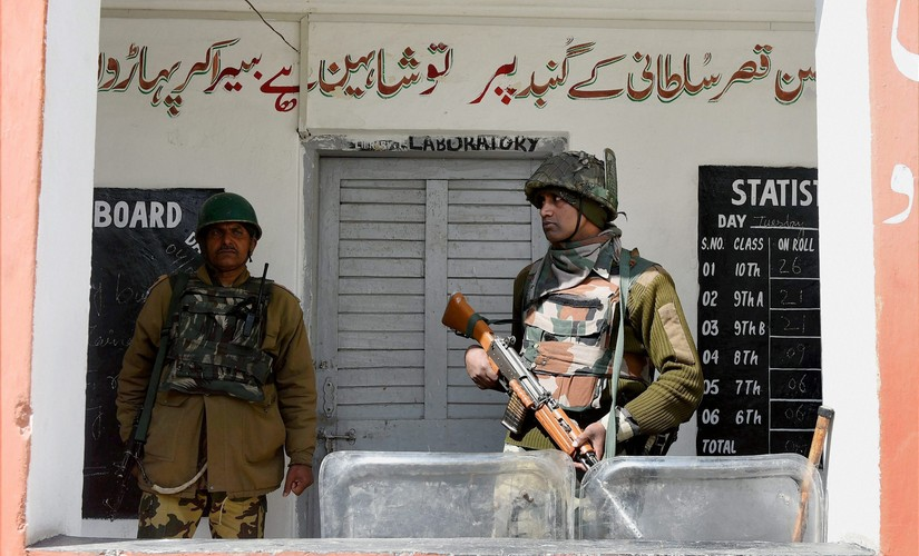 A jawan stands guard outside a polling station in Srinagar. PTI