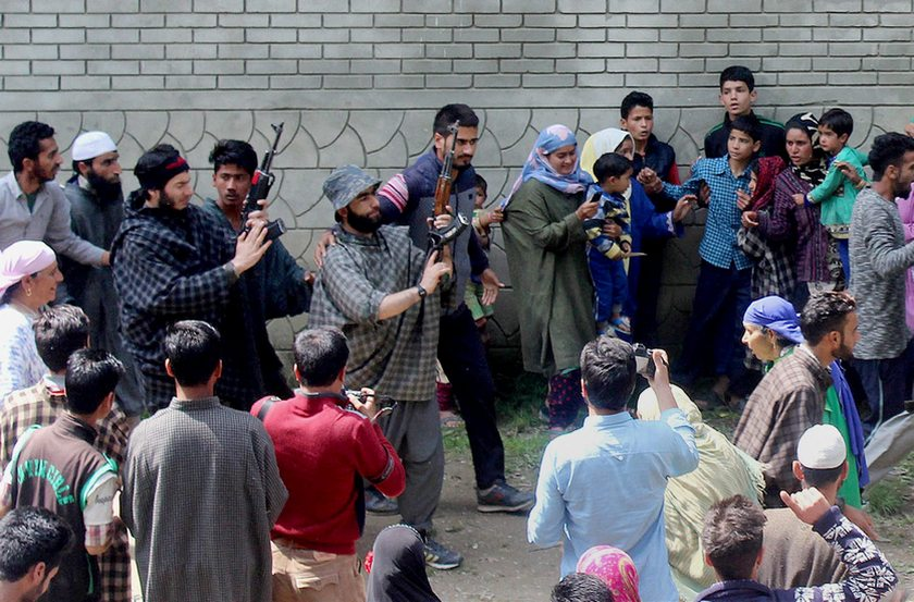 Kulgam: Suspected militants brandish their guns and shout slogans at the funeral of a slain colleague, killed in a shootout with the police, at Qoimoh in Kulgam district of south Kashmir on Sunday. PTI