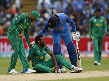 Pakistan's Wahab Riaz clutches his ankle who is attended by teammate Mohammad Amir and India's Yuvraj Singh. Reuters