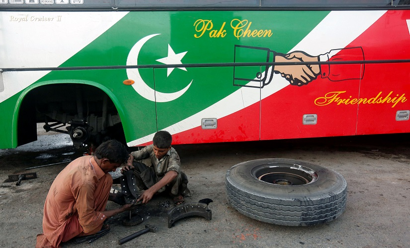 Workers sit on ground as they repair a bus brake shoes displaying the Pak China friendship sign along a road in Karachi Pakistan