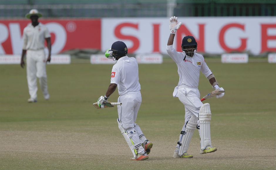 Sri Lanka's Dilruwan Perera, right, and Asela Gunaratne celebrate their team's victory over Zimbabwe by 4 wickets in their only test cricket match in Colombo, Sri Lanka. AP