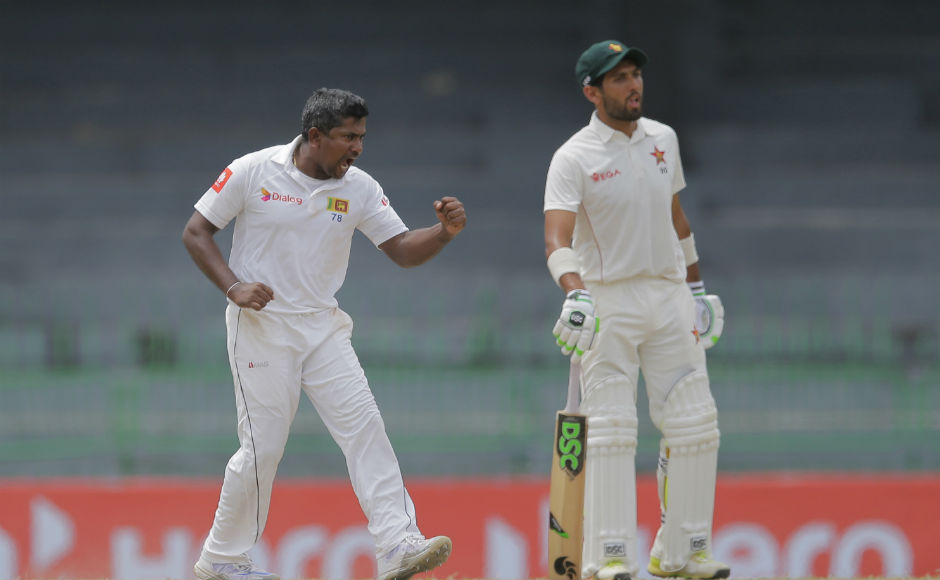 Sri Lanka's Rangana Herath, left, celebrates taking the wicket of Zimbabwe's Sean Williams as non striker Sikandar Raza watches during the third day's play. AP