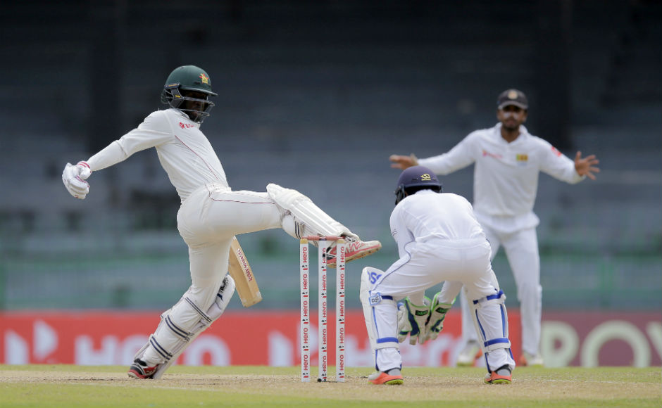 Zimbabwe's Donald Tiripano attempts to kick the ball to avoid it being hit the wicket during the second day's play of the one-off cricket test match. AP