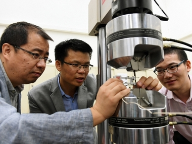The research team uses a tensile machine to test the yield strength and elongation of steel. (From right): Dr He Binbin, Dr Huang Mingxin and Dr Luo Haiwen. The University of Hong Kong