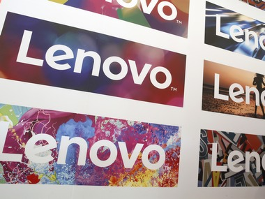 A man uses his laptop next to Lenovo's logos during the Mobile World Congress in Barcelona, Spain February 25, 2016. REUTERS/Albert Gea - RTX28K1H