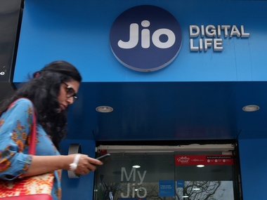 A woman checks her mobile phone as she walks past a mobile store of Reliance Industries' Jio telecoms unit, in Mumbai, India, July 11, 2017. REUTERS/Shailesh Andrade - RTX3AZ0Z