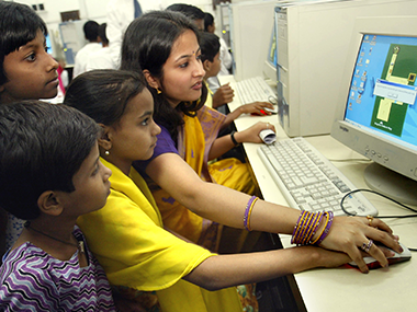 A trainer teaches children to use a computer. Reuters