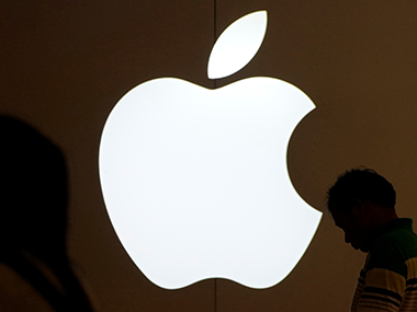 People standing in front of an Apple logo. Reuters