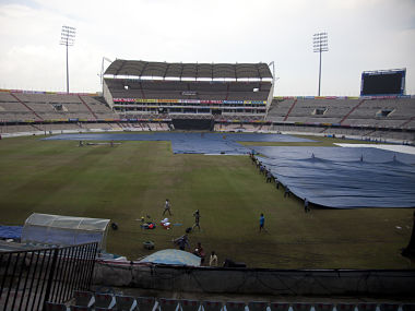 Indian groundsmen covers the pitch with plastic sheets ahead of third match between India and Australia in Hyderabad. AP