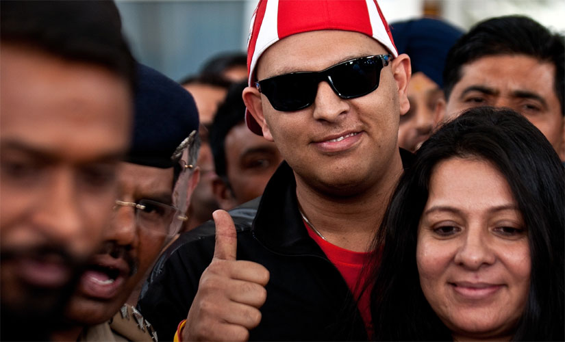 Yuvraj Singh gestures upon returning to India after treatment for a cancerous tumour in the US. His mother Shabnam Singh is in the foreground. AFP