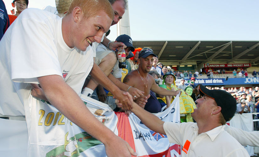 "Australia's Shane Warne meets with England cricket fans from the ""barmy army"" after their win over Engalnd in the third Ashes cricket test in Perth December 1, 2002. Reuters"