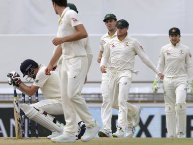 England's James Anderson, left, crouches after being hit on the helmet by Pat Cummins on Monday. AP