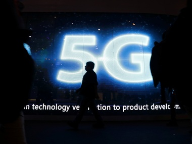 A visitor walks past a 5G sign during Mobile World Congress in Barcelona. Reuters