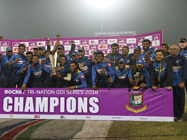 Sri Lanka's players and team officials pose for a group photo while celebrating with the trophy after winning the final match against Bangladesh of the Tri-Nation one-day international cricket series in Dhaka, Bangladesh, Saturday, Jan. 27, 2018. (AP Photo/A.M. Ahad)