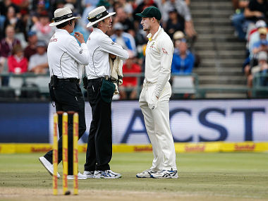 Australian fielder Cameron Bancroft (R) is questioned by Umpires Richard Illingworth (L) and Nigel Llong (C) during the third day of the third Test cricket match between South Africa and Australia at Newlands cricket ground on March 24, 2018 in Cape Town. / AFP PHOTO / GIANLUIGI GUERCIA