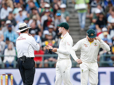Australian fielder Cameron Bancroft (R) is questioned by Umpires Richard Illingworth (L) and Nigel Llong (not in picture) during the third day of the third Test cricket match between South Africa and Australia at Newlands cricket ground on March 24, 2018 in Cape Town. / AFP PHOTO / GIANLUIGI GUERCIA
