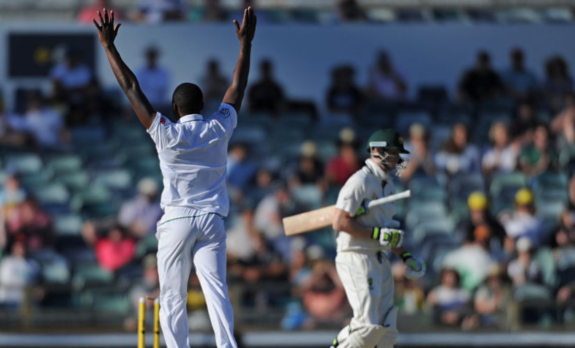 South Africa's Kagiso Rabada (L) celebrates dismissing Australia's Steve Smith (R) on day four of the first Test cricket match between Australia and South Africa in Perth on November 6, 2016. / AFP PHOTO / Greg Wood / IMAGE RESTRICTED TO EDITORIAL USE - STRICTLY NO COMMERCIAL USE