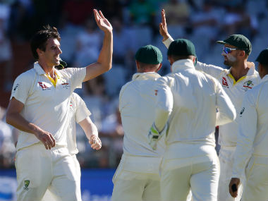 Australia's Pat Cummins celebrates with teammates after taking a wicket. AFP