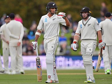 New Zealand's Tom Latham (R) walks off the field with teammate Jeet Raval (C) after play was stopped for bad light, during day four of the second cricket Test match between New Zealand and England at Hagley Oval in Christchurch on April 2, 2018. / AFP PHOTO / Marty MELVILLE