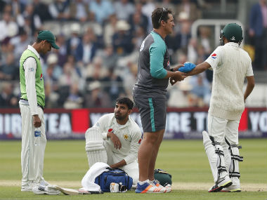 Pakistan's Babar Azam (R) receives treatment after being hit on the arm by a ball off the batting of England's Ben Stokes on the second day of the first Test match against England at Lord's. AFP