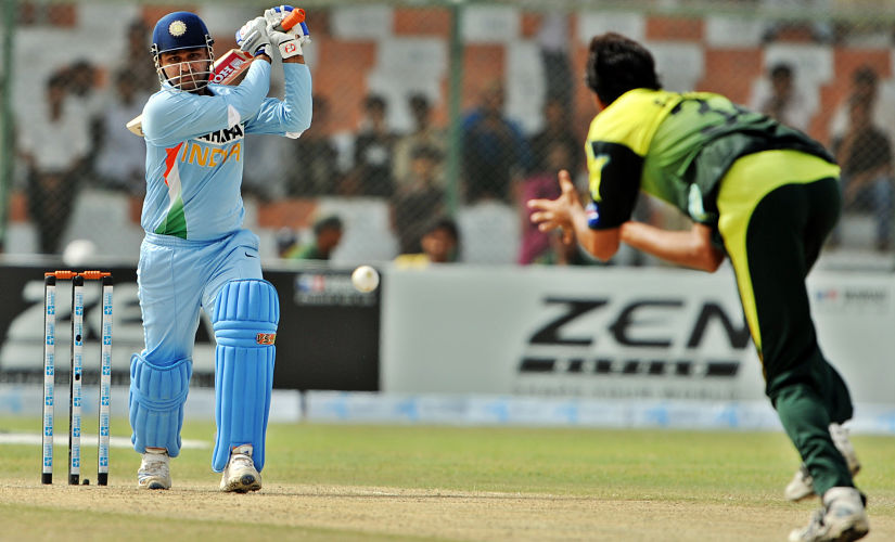 Indian cricketer Virender Sehwag (L) plays a stroke during the Super League Asia Cup match between Pakistan and India at the National Stadium in Karachi on July 2, 2008. Pakistan suffered a major blow as their captain Shoaib Malik was ruled unfit in their crucial Asia Cup Super League match against India, who won the toss and opted to bat. AFP PHOTO/Aamir QURESHI / AFP PHOTO / AAMIR QURESHI