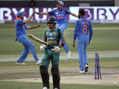 India's captain Rohit Sharma, left, celebrates with teammates the dismissal of Pakistan's Babar Azam, front, during the one day international cricket match of Asia Cup between India and Pakistan in Dubai, United Arab Emirates, Sunday, Sept. 23, 2018. (AP Photo/Aijaz Rahi)