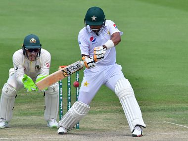 Pakistan cricketer Babar Azam (R) plays a shot as Australian wicketkeeper Tim Paine looks on during day three of the second Test cricket match in the series between Australia and Pakistan at the Abu Dhabi Cricket Stadium in Abu Dhabi on October 18, 2018. (Photo by GIUSEPPE CACACE / AFP)
