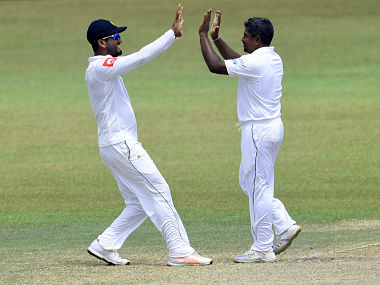 Sri Lankan cricketer Rangana Herath (R) celebrates with teammates Dimuth Karunaratne (L) after he dismissed South Africa's Dale Steyn during the fourth day of the second Test match between Sri Lanka and South Africa at the Sinhalese Sports Club (SSC) international cricket stadium in Colombo on July 23, 2018. (Photo by ISHARA S. KODIKARA / AFP)