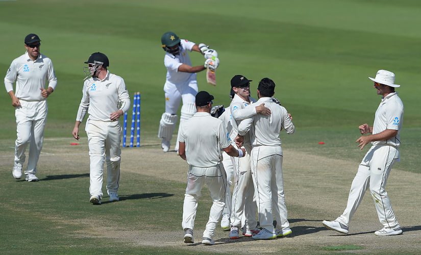 New Zealand cricketers celebrate after the dismissal of Pakistani cricketer Bilal Asif (back C) during the fourth day of the first Test cricket match between Pakistan and New Zealand at the Sheikh Zayed International Cricket Stadium in Abu Dhabi on November 19, 2018. (Photo by AAMIR QURESHI / AFP)