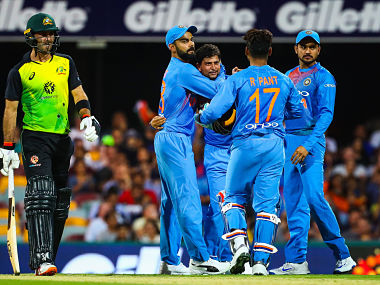 India's Kuldeep Yadav (C) is embraced by captain Virat Kohli (2nd L) as they celebrate the caught and bowled wicket of Australia's Chris Lynn during the T20 international cricket match between Australia and India in Brisbane on November 21, 2018. (Photo by Patrick HAMILTON / AFP) / -- IMAGE RESTRICTED TO EDITORIAL USE - STRICTLY NO COMMERCIAL USE --