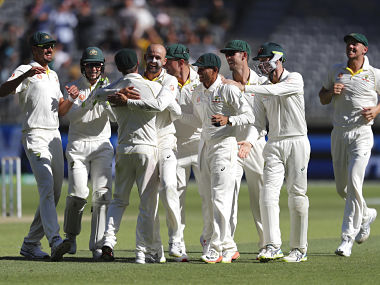 Australian players congratulate bowler Nathan Lyon, centre, after he claimed the wicket of India's Virat Kohli during play in the second cricket test between Australia and India in Perth, Australia, Monday, Dec. 17, 2018. (AP Photo/Trevor Collens)