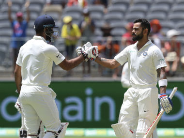 Virat Kohli's congratulated by partner Hanuma Vihari after completing his century on Day 3. AP