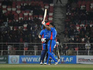 Afghan batsman Hazratullah Zazai raises his bat to celebrate a record breaking scoring run during Afghanistan's International Twenty20 (T20) cricket match against Ireland in the northern Indian city of Dehradun on February 23, 2019. - Hazratullah Zazai smashed the ball to every corner of the ground, and even out of the stadium, as Afghanistan racked up a world record T20 score of 278-3 in a crushing demolition of Ireland on February 23. (Photo by STR / AFP) / ----IMAGE RESTRICTED TO EDITORIAL USE - STRICTLY NO COMMERCIAL USE----- / GETTYOUT