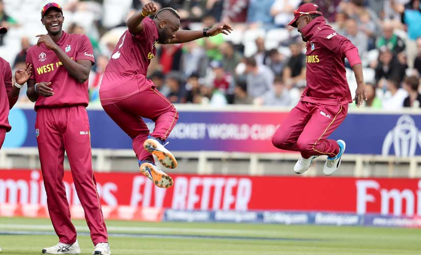 West Indies' bowler Andre Russell celebrates taking the wicket of Pakistan's Haris Sohail with Darren Bravo. AP