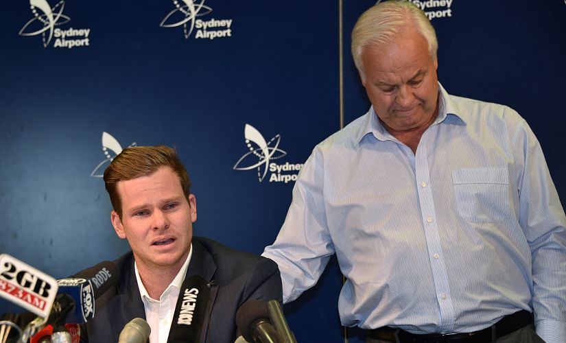 """Cricketer Steve Smith (L) is comforted by his father Peter as he reacts at a press conference at the airport in Sydney on March 29, 2018, after returning from South Africa. - Distraught Australian cricketer Steve Smith on March 29 accepted full responsibility for a ball-tampering scandal that has shaken the sport, saying he was devastated by his """"big mistake"""". (Photo by PETER PARKS / AFP) / -- IMAGE RESTRICTED TO EDITORIAL USE - STRICTLY NO COMMERCIAL USE --"""