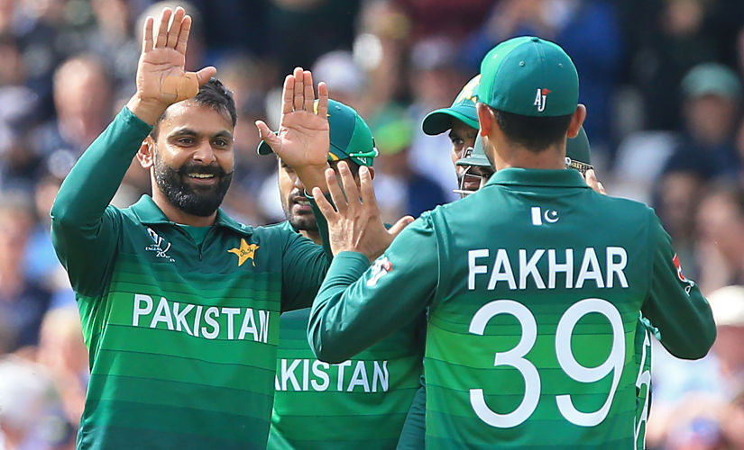 Mohammad Hafeez (L) celebrates with teammates after taking the wicket of England's captain Eoin Morgan. AFP