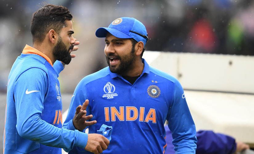 India's captain Virat Kohli (L) speaks with teammate Rohit Sharma as they walk off the field as rain stops play during the 2019 Cricket World Cup group stage match between India and Pakistan at Old Trafford in Manchester, northwest England, on June 16, 2019. (Photo by Dibyangshu SARKAR / AFP) / RESTRICTED TO EDITORIAL USE