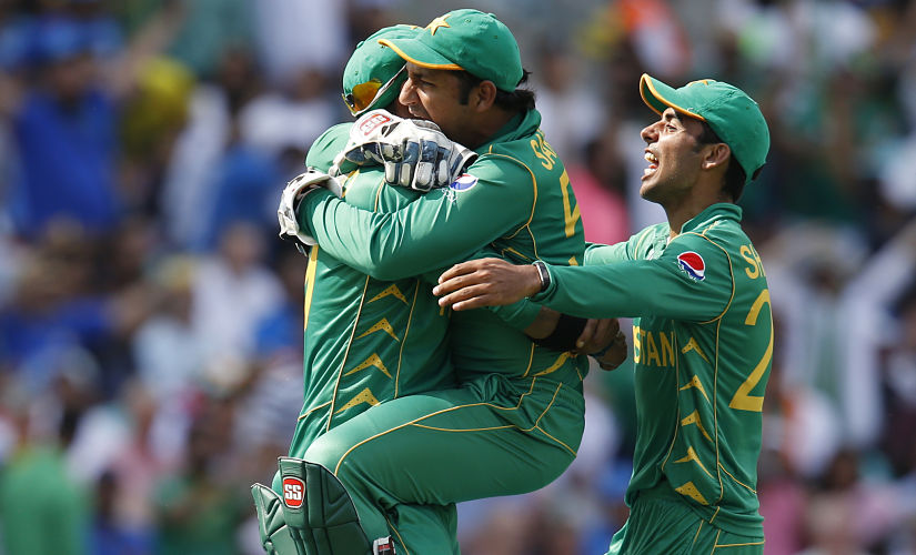 Pakistan's Shadab Khan (R) and Pakistan's Sarfraz Ahmed (C) celebrate with Pakistan's Imad Wasim after he catches India's MS Dhoni during the ICC Champions Trophy final cricket match between India and Pakistan at The Oval in London on June 18, 2017. - Title-holders India were set a target of 339 to win the Champions Trophy final against Pakistan at The Oval on Sunday. (Photo by Ian KINGTON / AFP) / RESTRICTED TO EDITORIAL USE