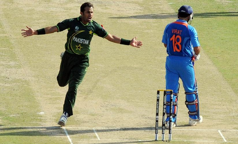 Pakistani fast bowler Wahab Riaz (L) celebrates after taking the wicket of Indian cricketer Virat Kohli during the ICC Cricket World Cup 2011 semi-final match between India and Pakistan at The Punjab Cricket Association (PCA) Stadium in Mohali on March 30, 2011 AFP PHOTO/ MANAN VATSYAYANA (Photo by MANAN VATSYAYANA / AFP)