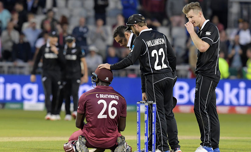 West Indies' Carlos Brathwaite (C) is consoled by New Zealand players having fallen short in the run-chase during the 2019 Cricket World Cup group stage match between West Indies and New Zealand at Old Trafford in Manchester, northwest England, on June 22, 2019. (Photo by Dibyangshu Sarkar / AFP) / RESTRICTED TO EDITORIAL USE