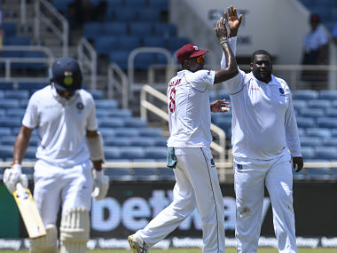Jason Holder (C) and Rahkeem Cornwall (R) of West Indies celebrate the dismissal of Cheteshwar Pujara (L) of India during day 1 of the 2nd Test between West Indies and India at Sabina Park, Kingston, Jamaica, on August 30, 2019. (Photo by Randy Brooks / AFP)