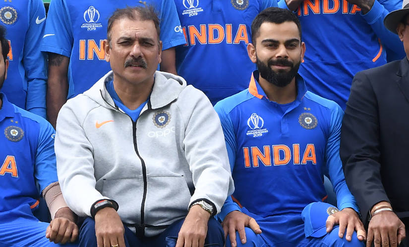 India's head coach Ravi Shastri (L) and India's captain Virat Kohli (R) pose for a group photograph with India team and management ahead of the 2019 Cricket World Cup group stage match between Sri Lanka and India at Headingley in Leeds, northern England, on July 6, 2019. (Photo by Dibyangshu Sarkar / AFP) / RESTRICTED TO EDITORIAL USE