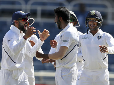 India's Jasprit Bumrah, center, is congratulated by captain Virat Kohli for his hat-trick wicket, by the dismissal of West Indies' Roston Chase, during day two of the second Test cricket match at Sabina Park cricket ground in Kingston, Jamaica Saturday, Aug. 31, 2019. (AP Photo/Ricardo Mazalan)
