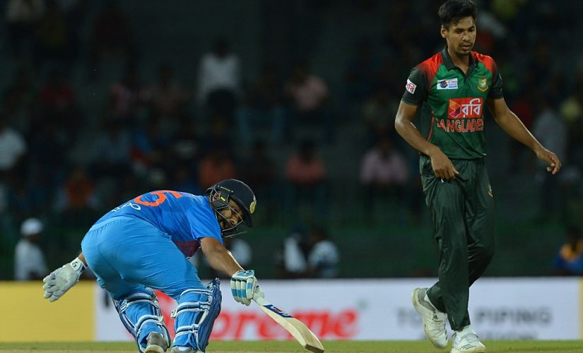 Indian cricket captain Rohit Sharma (L) runs between the wickets as Bangladesh cricketer Mustafizur Rahman look on during the fifth Twenty20 (T20) international cricket match between India and Bangladesh of the tri-nation Nidahas Trophy at the R. Premadasa stadium in Colombo on March 14, 2018. (Photo by LAKRUWAN WANNIARACHCHI / AFP)