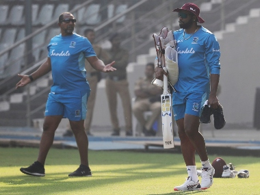 West Indies cricket team coach Phil Simmons , left, speaks with Kieron Pollard during a training session. AP