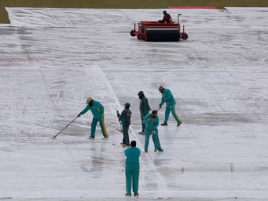 Groundkeepers work to remove water from covers following overnight heavy rainfalls during the third day of the Test between Pakistan and Sri Lanka. AP