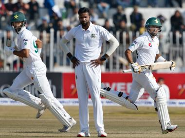 Pakistan batsmen Shan Masood, left, and Babar Azam, right, run between the wickets as Bangladesh pacer Ebadot Hossain looks on during their second day of the 1st test cricket match at Rawalpindi cricket stadium in Rawalpindi, Pakistan, Saturday, Feb. 8, 2020. (AP Photo/Anjum Naveed)