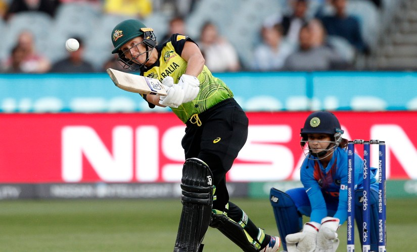 Australia's Alyssa Healy, left, drives the ball in front of India's Tanya Bhatia during the Women's T20 World Cup final against India in Melbourne, Australia. AP