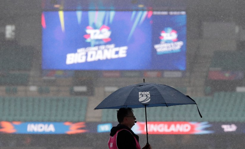 A worker stands under an umbrella as rain falls on the Sydney Cricket Ground delaying the start of the Women's T20 World Cup cricket semifinal matches in Sydney. AP